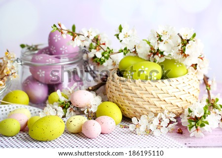 Composition with Easter eggs in glass jar and wicker basket, and blooming branches on light background - stock photo