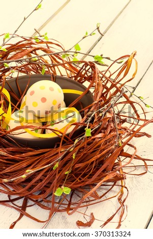Composition with Easter eggs in nest, on boards background, tinted