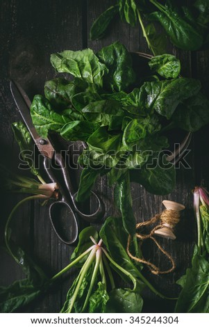 Composition with fresh spinach, old scissors and spool of thread over wooden surface. Top view. Dark rustic style with retro filter effect - stock photo