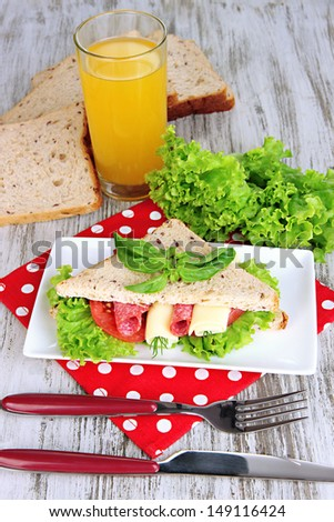 Composition with fruit juice and tasty sandwich with salami sausage and vegetables on color napkin, on wooden  table background - stock photo