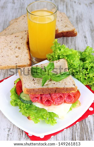 Composition with fruit juice and tasty sandwich with salami sausage and vegetables on color napkin, on wooden  table, on bright background