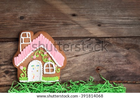 Composition with gingerbread house and paper grass on a wooden table - stock photo
