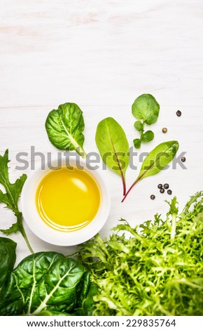 Composition with green herb salad and bowl with oil, food background with place for text - stock photo