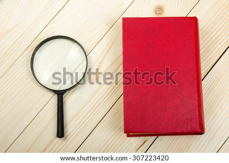 Composition with hardback book and magnifying glass on the table. Back to school, copy space. Education background. - stock photo