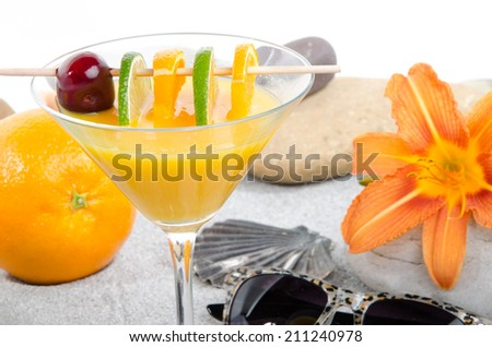 Composition with healthy orange cocktail on a beach environment