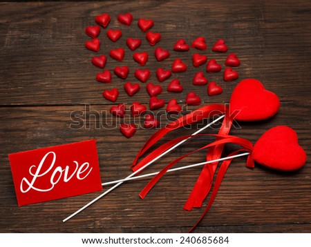 Composition with hearts and postcard with the word Love. Can be used as greeting card for Valentine's Day - stock photo