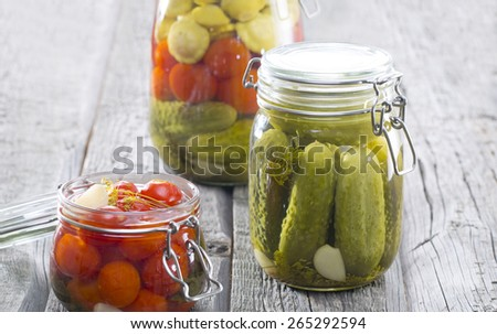 Composition with jars of pickled vegetables on wooden tables. Marinated food - stock photo
