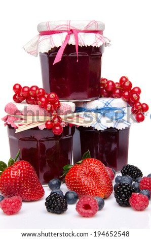 Composition with jars of red and black fruits jams and fresh fruits, isolated on white - stock photo