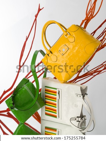 composition with leather bags in white, yellow and green colors with reflection - stock photo
