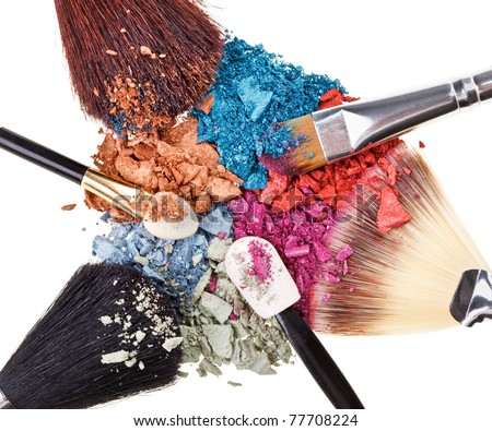 Composition with makeup brushes and broken multicolor eye shadows - stock photo