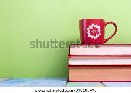 Composition with old vintage hardback books and red cup with yellow heart shape and pencils on wooden deck table and green background. Books stacking. Back to school. Copy Space. Education background. - stock photo