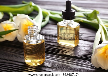Composition with perfume and flowers on wooden table