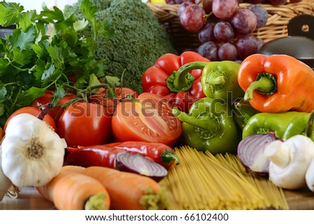Composition with raw vegetables and spaghetti on kitchen table - stock photo
