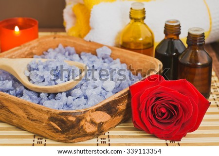 Composition with sea salt, extracts of medicinal roots, candle and flower - stock photo