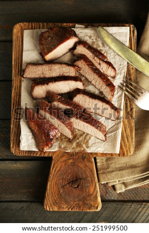 Composition with sliced roasted meat on cutting board on wooden background - stock photo