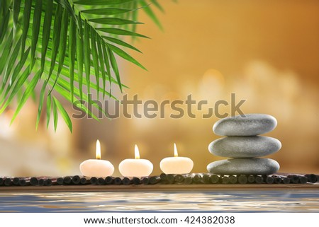 Composition with spa stones and candles on blurred background - stock photo
