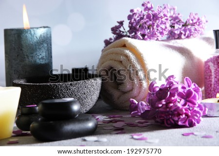 Composition with spa treatment, towels and lilac flowers, on wooden table, on light background - stock photo