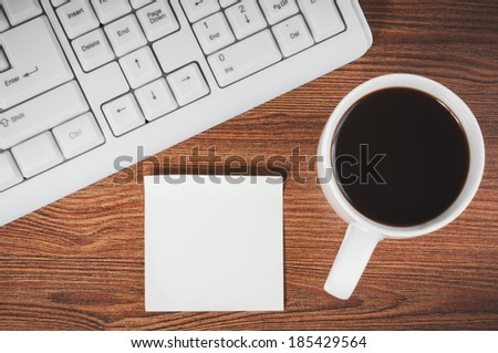 Composition with sticker, the cup of coffee and keyboard laying on wooden desk - stock photo