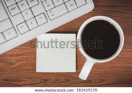 Composition with sticker, the cup of coffee and keyboard, laying on wooden desk - stock photo