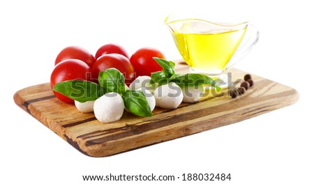 Composition with tasty mozzarella cheese balls, basil and red tomatoes, olive oil on cutting board, isolated on white - stock photo