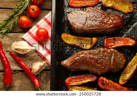 Composition with tasty roasted meat and sliced pepper on pan, tomatoes and rosemary sprigs on wooden background - stock photo