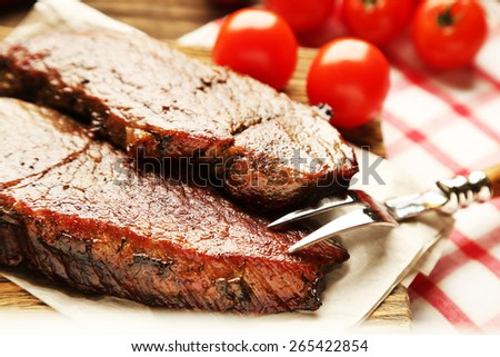 Composition with tasty roasted meat on cutting board, tomatoes and rosemary sprigs on wooden background - stock photo