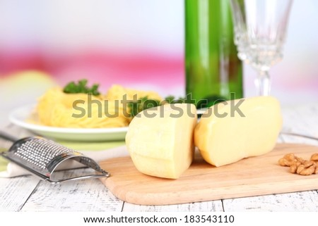 Composition with tasty spaghetti, grater, cheese, wine bottle and glass on wooden table, on light background