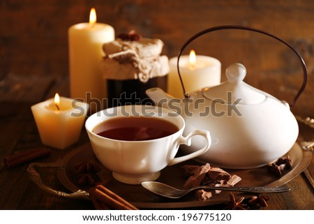 Composition with tea in cup and teapot and candles on table, on wooden background - stock photo