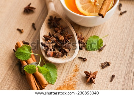 Composition with tea in cup, cinnamon, cloves and wooden background - stock photo