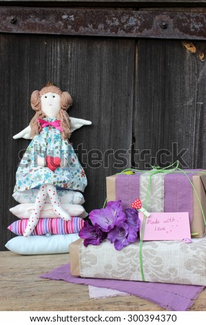 Composition with textile objects: wrapped gift box and doll - stock photo