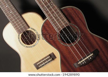 Composition with two ukuleles focus on the ukulele right