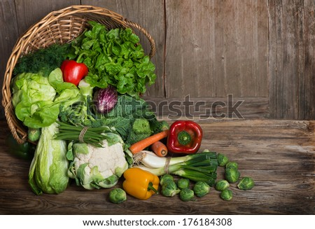 Composition with vegetables  in wicker basket on the wooden table - stock photo