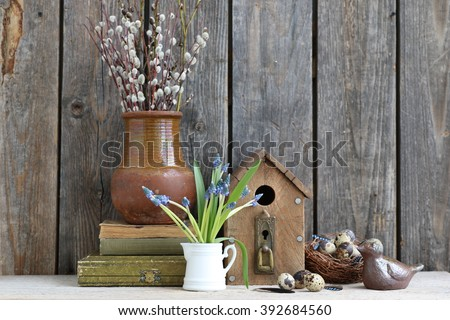 Composition with very old Russian jag, branch of willows,wooden bird house, nest,quail eggs, ceramic bird, fresh blue flowers in the small white pitcher, old books - stock photo