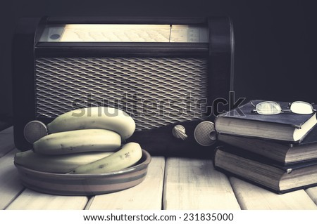 Composition with vintage items on table Vintage radio, books, glasses and bananas on wooden surface. Edited image with vintage effect - stock photo