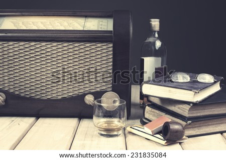 Composition with vintage items on table Vintage radio, books, glasses tobacco pipe and whiskey on wooden surface. Edited image with vintage effect - stock photo