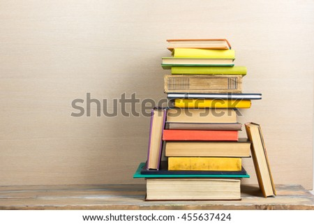 Composition with vintage old hardback books, diary, fanned pages on wooden deck table and beige background. Books stacking. Back to school. Copy Space. Education background. - stock photo
