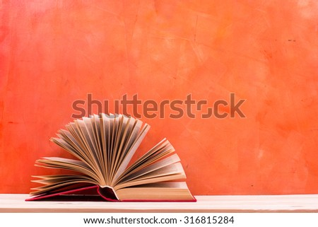 Composition with vintage old hardback books, diary, fanned pages on wooden deck table and red background. Books stacking. Back to school. Copy Space. Education background - stock photo