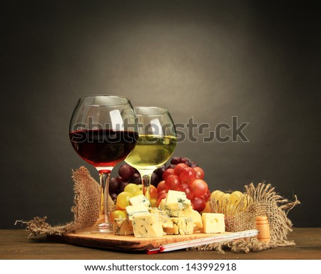 Composition with wine, blue cheese and grape on wooden table, on grey background - stock photo