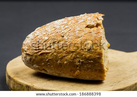 Composition with wooden kitchen cutting board and organic bread on dark background