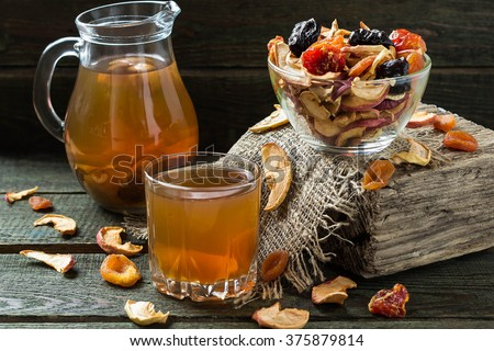 Compote of dried fruits in the jug and mug and assorted dried fruits in bowl on wooden table. Selective focus - stock photo