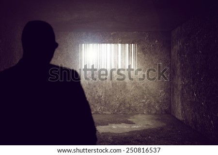 Compulsive Consumerism Concept, Businessman locked in Concrete Prison Cell with Bar code shaped Window. Sun rays and sun flare through the prison bars, selective focus.