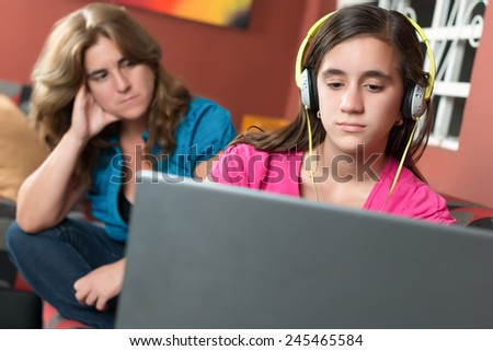 Computer addiction - Teenage girl using a laptop and ignoring her worried mother - stock photo