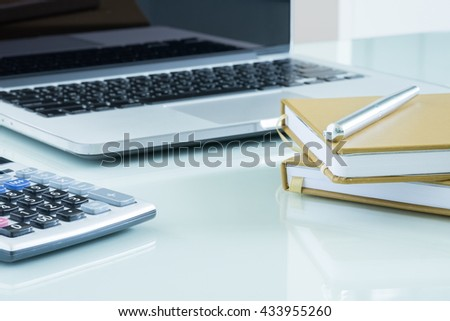 computer and brown notebook with office supplies on white table - stock photo