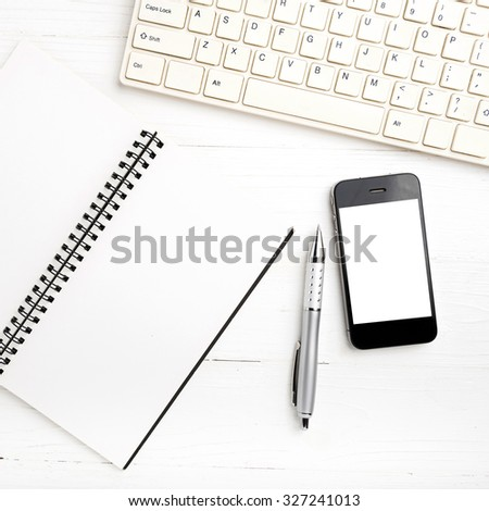 computer and cellphone with notebook and pen over white table