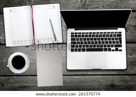computer and cup of coffee on wooden table - stock photo