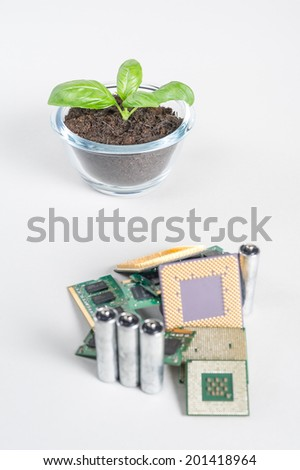 Computer and electronic waste recycling concept. Detailed shot with focus on freshly grown plant - stock photo