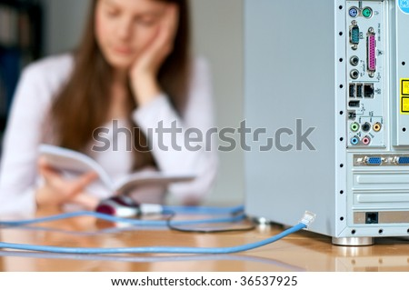 computer back side and woman with cable and instruction manual - stock photo
