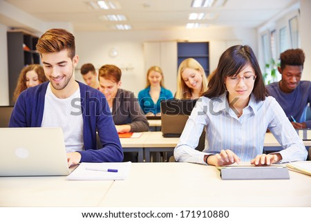 Computer class in university with many students with laptops and tablet PCs - stock photo