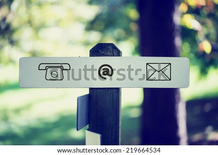 Computer Contact Icons Sign Affixed to Wooden Outdoor Signpost. - stock photo
