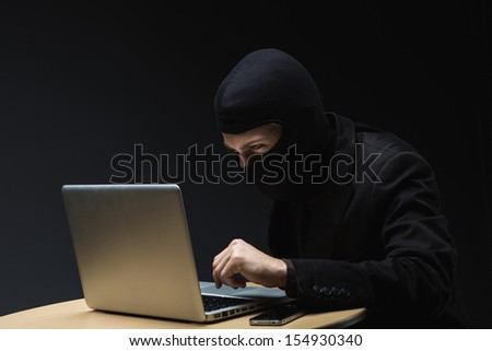 Computer criminal or hacker in a balaclava sitting at a desk in the darkness stealing information off a laptop computer and copying it onto a small hard drive - stock photo